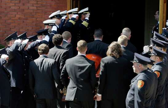 An honor guard from area fire departments salute as pallbearers carry the casket of Boston Marathon bomb victim Krystle Campbell, 29, into St. Joseph's Church for her funeral in Medford, Mass. Monday, April 22, 2013. Photo: Elise Amendola