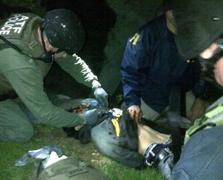 In this Friday, April 19, 2013 photo taken by the Massachusetts State Police, obtained by The Associated Press and authenticated by a member of the Bureau of Alcohol, Tobacco, Firearms and Explosives, ATF and FBI agents check suspect Dzhokhar Tsarnaev for explosives and also give him medical attention after he was apprehended in Watertown, Mass., at the end of a tense day that began with his older brother, Tamerlan, dying in a getaway attempt. Tsarnaev lay hospitalized in serious condition under heavy guard Saturday as investigators continue piecing together the who and why of the two brothers involved in the deadly Boston Marathon bombings. Photo: Massachusetts State Police