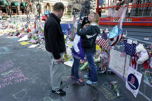 Holly Holland, right, hugs her daughter Katie, center, as her husband Kevin Holland, left, all of St. Louis,  looks while visiting a makeshift memorial in Boston, Monday, April 22, 2013. The memorial sits on Boylston St., not far from where two bombs exploded near the finish line of the Boston Marathon, Monday, April 15, 2013. Photo: Steven Senne