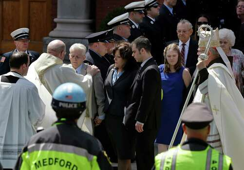 A priest comforts family members of Boston Marathon bomb victim Krystle Campbell after her funeral at St. Joseph's Church in Medford, Mass. Monday, April 22, 2013. At center is her mother, Patty Campbell, and her brother, Billy. At far right is Boston Cardinal Sean O'Malley. Photo: Elise Amendola