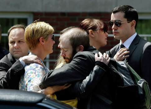 Mourners hug as they leave the funeral for Boston Marathon bomb victim Krystle Campbell, 29, at St. Joseph's Church in Medford, Mass. Monday, April 22, 2013. Hundreds of family and friends packed the church in Medford, Mass., for Campbell's funeral, while dozens more waited outside after being turned away. Photo: Elise Amendola
