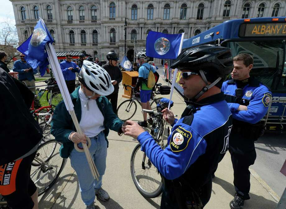 Albany Police bike patrolman B. Henley, right borrows a an Earth Day flag for his bike on Earth Day April 22, 2013 in Albany, N.Y.    (Skip Dickstein/Times Union) Photo: SKIP DICKSTEIN / 10022016A