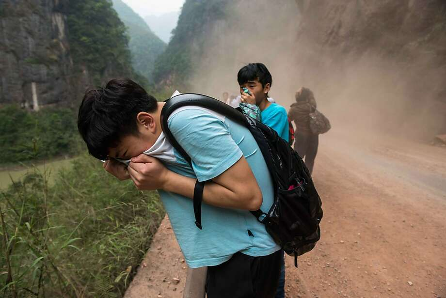 Youths cover their mouths and noses to avoid inhaling dust during rock slides outside the city of Ya'an, Sichuan province. Clogged roads, debris and landslides impeded rescuers searching for survivors of a powerful earthquake in mountainous southwest China that left at least 188 dead. Photo: Str, AFP/Getty Images