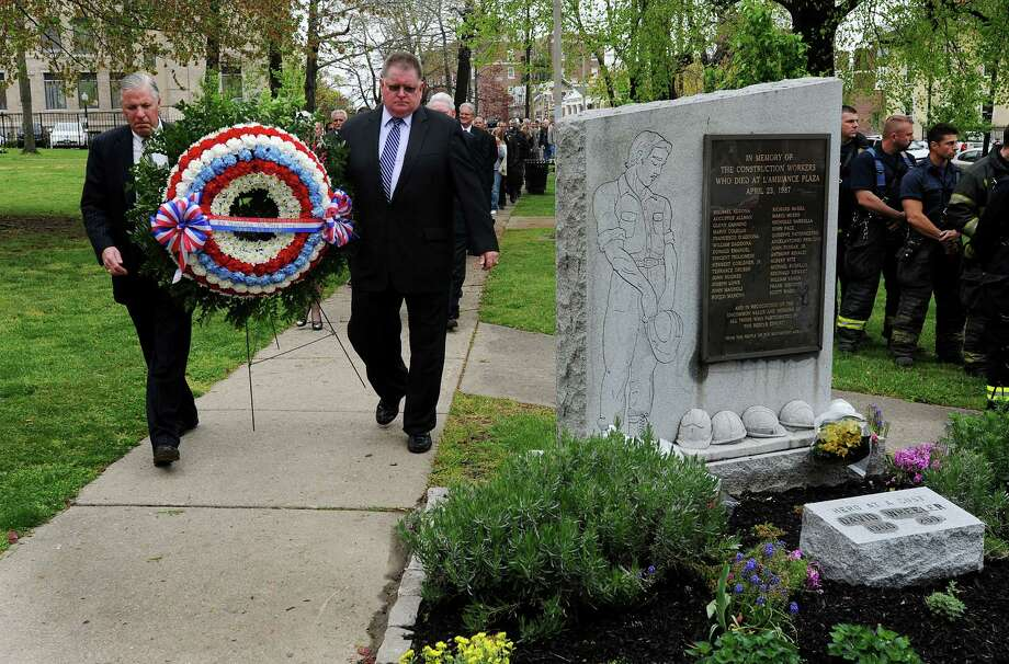 Tom Wilkinson and  Peter Carroll carry the wreath to the City Hall monument during the ceremony to honor the 25th Anniversary of the L'Ambiance Plaza collapse on Monday, April 23, 2012 in Bridgeport, Conn. City officials will mark the 26th anniversary of the collapse on Tuesday, April 23, 2013 at a 10:30 a.m. ceremony at City Hall, 45 Lyon Terrace. Photo: Cathy Zuraw, File Photo / Connecticut Post