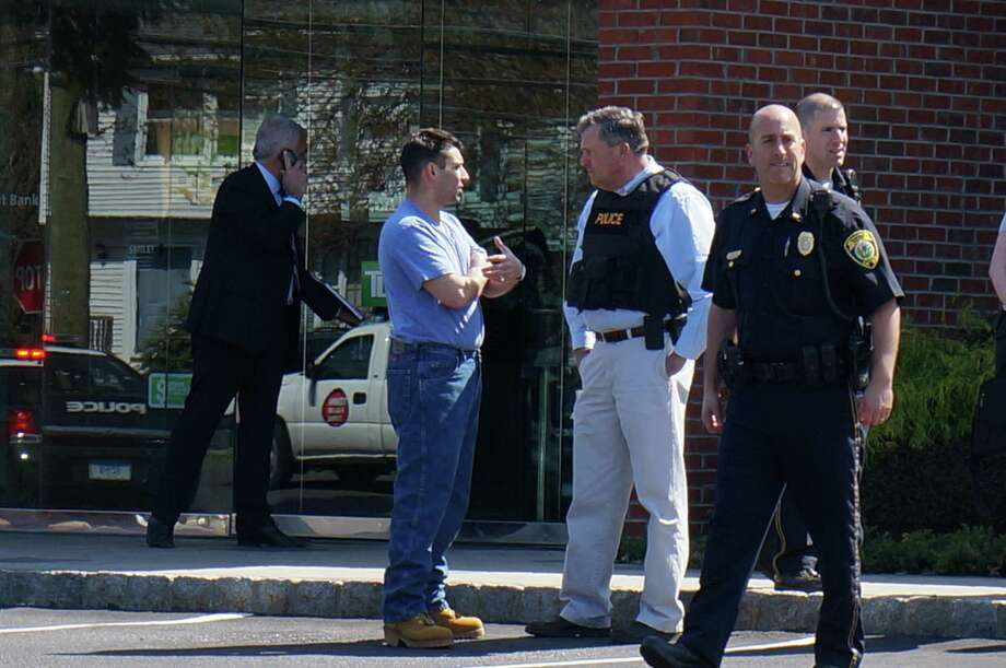 The victim of a kidnapping and robbery, in the light blue, short-sleeved shirt, talks with police in the parking lot of TD Bank on Black Rock Turnpike in Fairfield, Conn. on Monday April 22, 2013. Police are investigating a kidnapping and robbery that started in Bridgeport and ended at TD Bank. Photo: Genevieve Reilly / Fairfield Citizen
