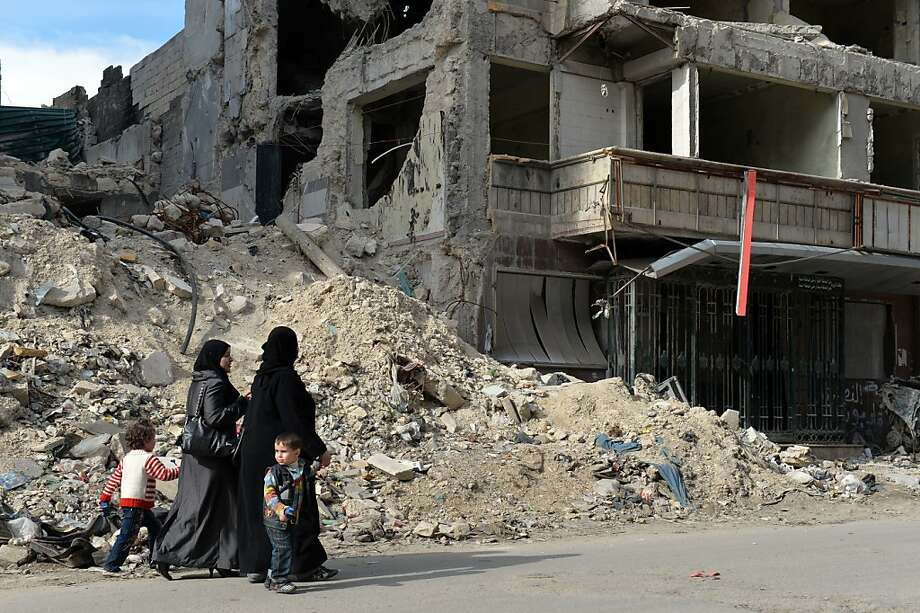 TOPSHOTS Syrian women walk past the destruction at Dar Al-Shifa hospital in the northern city of Aleppo on on April 21, 2013. Syria's National Coalition head Ahmad Moaz al-Khatib has refiled his resignation and an interim leader is being sought, a fellow member and a source close to the main opposition group said. AFP PHOTO / MIGUEL MEDINAMIGUEL MEDINA/AFP/Getty Images Photo: Miguel Medina, AFP/Getty Images