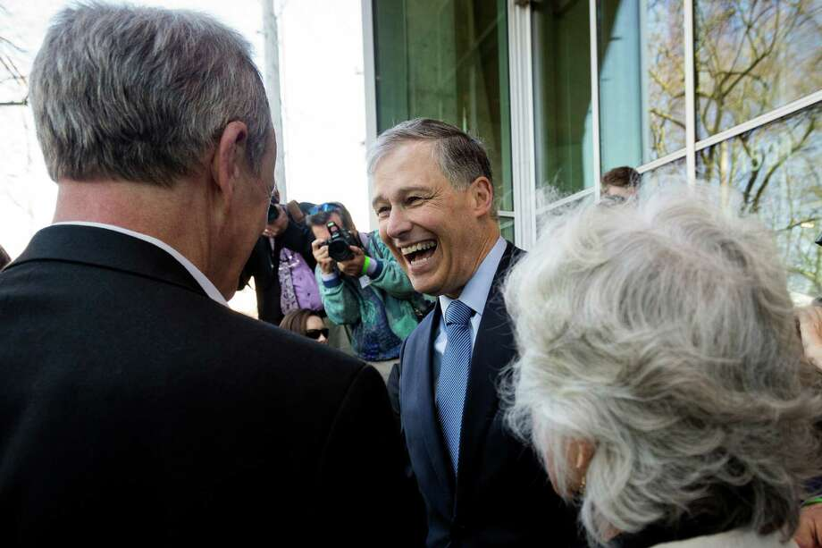 Gov. Jay Inslee, center, laughs during a media frenzy at the grand opening of the Bullitt Center on Earth Day Monday on Capitol Hill in Seattle. This six-story, 50,000 square-foot structure is the greenest commercial building in the world and aims to improve long-term environmental performance and efficiency through cutting-edge sustainable technology. Photo: JORDAN STEAD, SEATTLEPI.COM / SEATTLEPI.COM