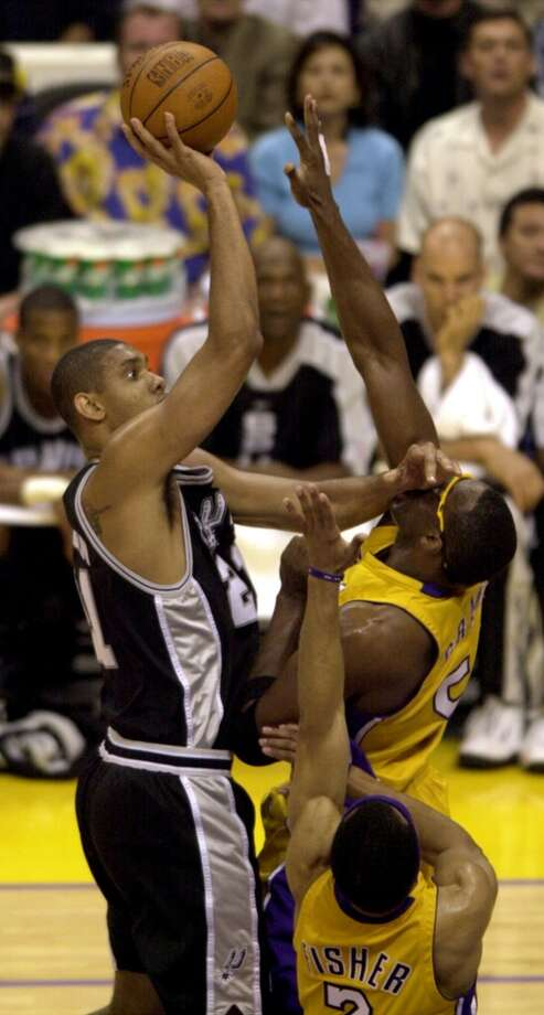 Tim Duncan shoots against the defense of  the Lakers\' Horace Grant and Derek Fisher (2) in Los Angeles Sunday May 27, 2001.