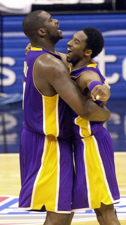 Lakers center Shaquille O\'Neal (left) and teammate Kobe Bryant embrace at mid court during the final second of their victory over the Spurs in Game 2 of the Western Conference finals in San Antonio, Monday, May 21, 2001.