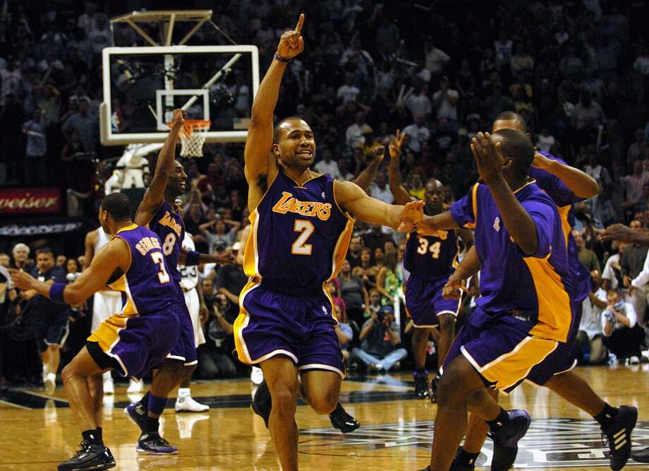 The Lakers\' Derek Fisher (2) celebrates with teammates after he hit the game winning shot as time expired to beat the Spurs 74-73 Game 5 of the Western Conference semifinals at the SBC Center on Thursday, May 13, 2004.