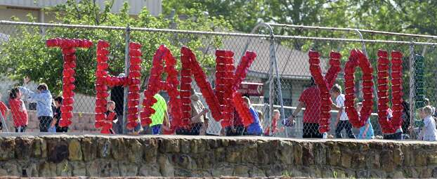 Staff at the West Elementary School put up a mesage made of cups on a fence as students students return to school in a town trying to get back to normalcy, on Monday April 22, 2013. Photo: Bob Owen, San Antonio Express-News / ©2013 San Antonio Express-News