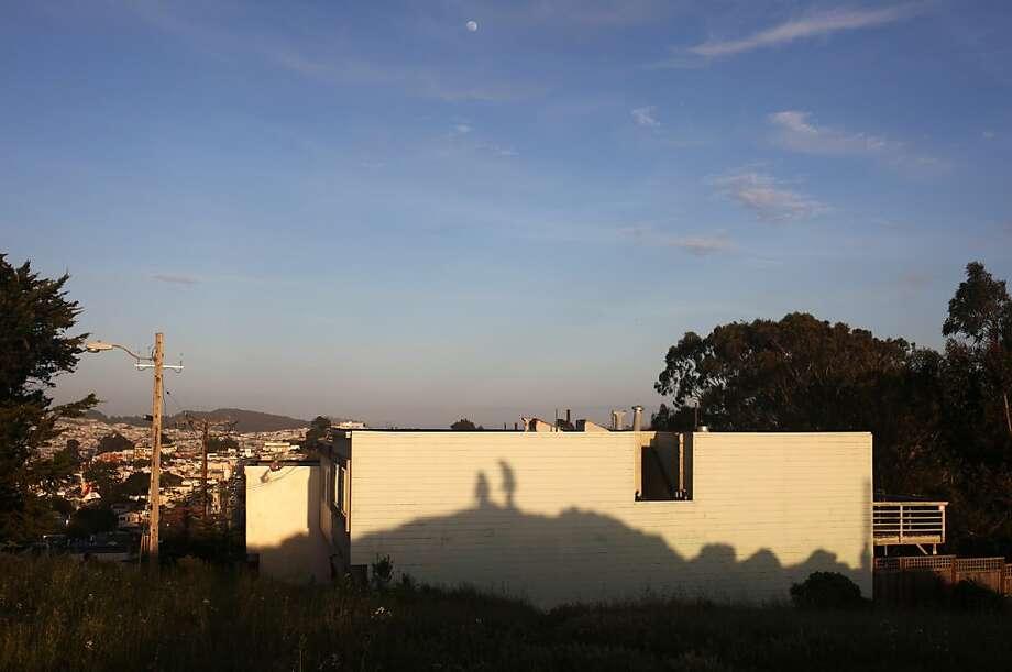 Kimberly and Porsha Lewis' silhouettes are cast on a wall of Lakeview   & Ashton Mini Park. Photo: Pete Kiehart, The Chronicle