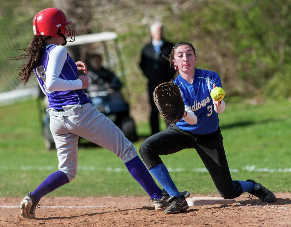 Fairfield Ludlowe high school tries to pickoff Westhill high school's Nicole Psichopaidas on first base but Reagan Walker doesn't get the throw in time during a softball game played at Sturges Field, Fairfield, CT on Monday April 22nd, 2013.