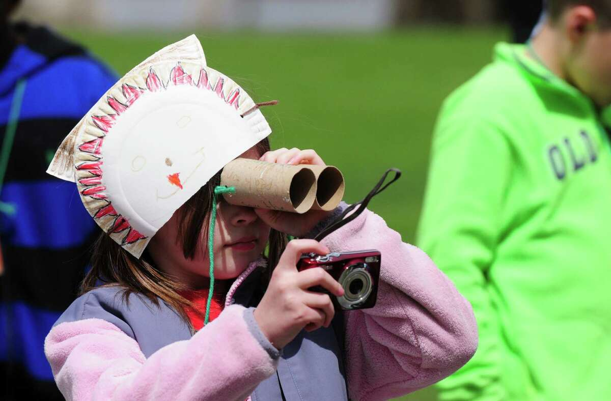 Menands School second grader Leilah Neuman, peers through self-styled binoculars during a kick off event to launch New York's Watchable Wildlife Program Monday, April 22, 2013, at Peebles Island State Park in Waterford, N.Y. The New York Wildlife Viewing Guide, which features more than 100 wildlife viewing locations, was also announced. (Will Waldron/Times Union)