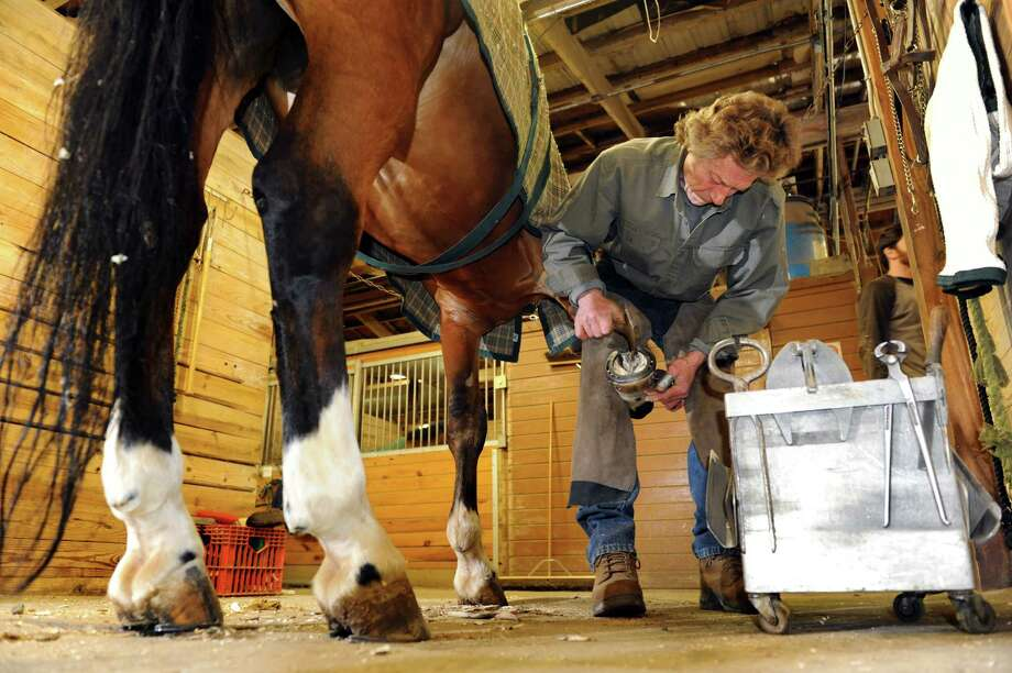 Farrier Jim Santore works to shoe Cedar, a schooling horse, on Tuesday, April 9, 2013, at Van Lennep Riding Center in Greenfield, N.Y. (Cindy Schultz / Times Union) Photo: Cindy Schultz / 10021904A