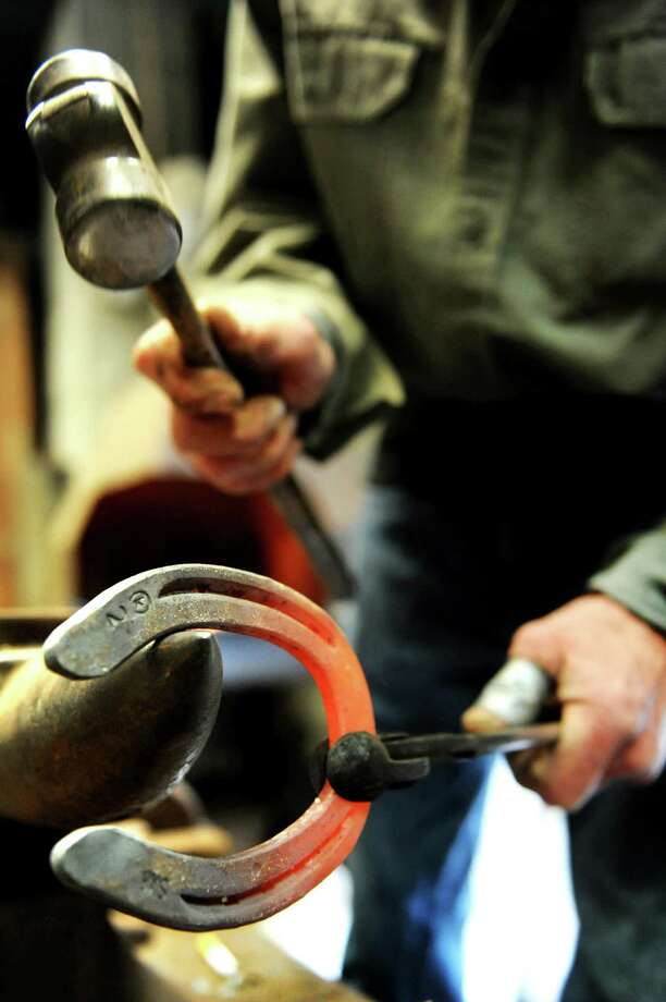Farrier Jim Santore hammers a hot horseshoe on Tuesday, April 9, 2013, at Van Lennep Riding Center in Greenfield, N.Y. (Cindy Schultz / Times Union) Photo: Cindy Schultz