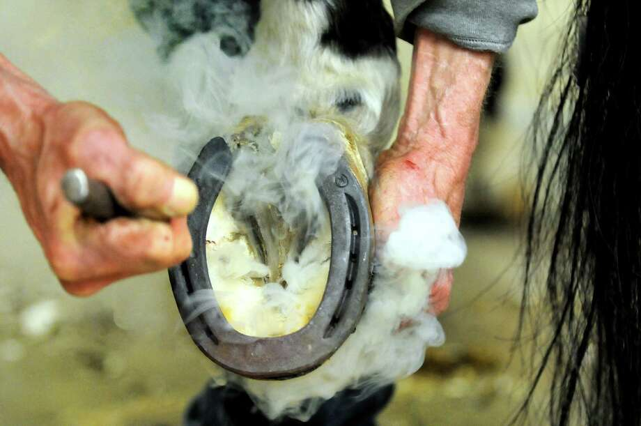 A hot shoe sears Tobey's bare hoof, which creates smoke, as farrier Jim Santore works on Tuesday, April 9, 2013, at Van Lennep Riding Center in Greenfield, N.Y. (Cindy Schultz / Times Union) Photo: Cindy Schultz / 10021904A