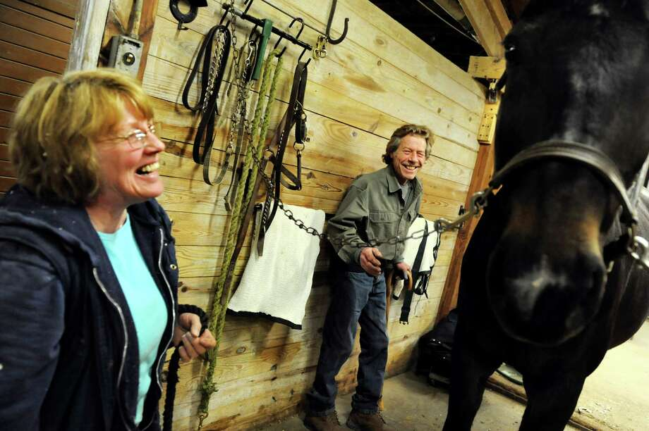 Barn manager Kathleen McGrath, left, laughs with farrier Jim Santore as she prepares to return Leroy to his stall on Tuesday, April 9, 2013, at Van Lennep Riding Center in Greenfield, N.Y. (Cindy Schultz / Times Union) Photo: Cindy Schultz / 10021904A