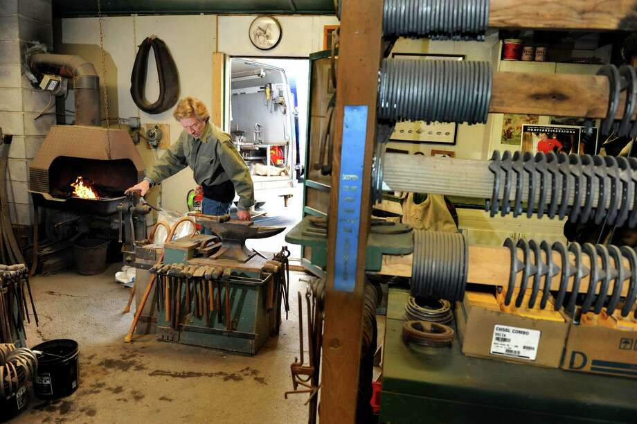 Farrier Jim Santore works with an open forge and anvil to shape horseshoes on Tuesday, April 9, 2013, at Van Lennep Riding Center in Greenfield, N.Y. (Cindy Schultz / Times Union) Photo: Cindy Schultz / 10021904A
