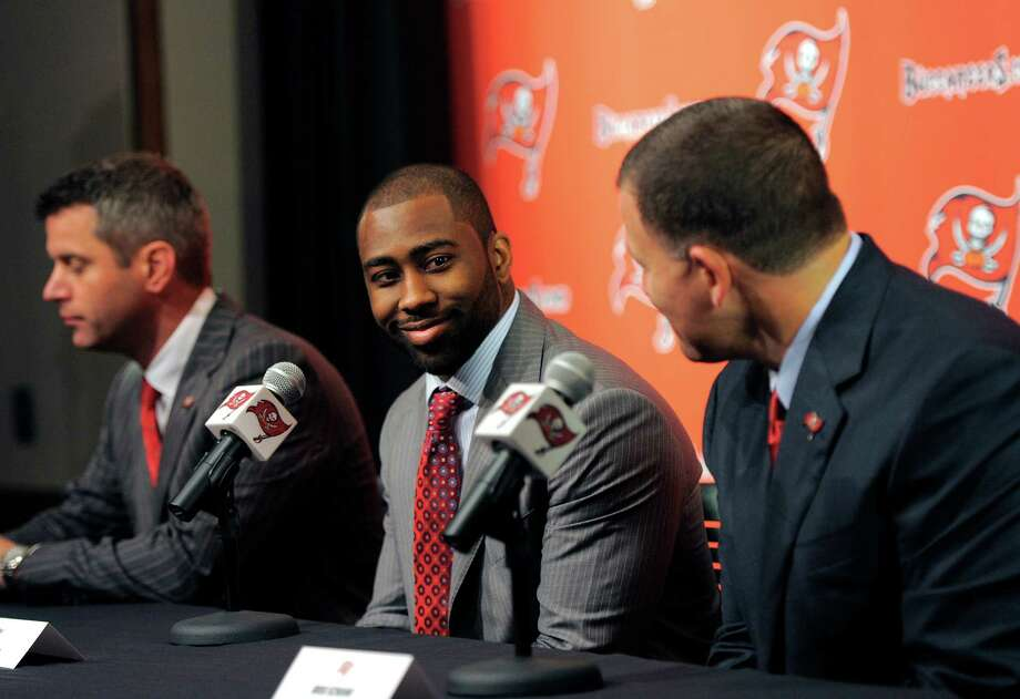 Tampa Bay Buccaneers general manager Mark Dominik, left, cornerback Darrelle Revis, center, and head coach Greg Schiano address the media while announcing that the Buccaneers have acquired Revis from the New York Jets during an NFL press conference Monday, April, 22, 2013, in Tampa, Fla. The Buccaneers and Revis have agreed on a six-year contract. (AP Photo/Brian Blanco) Photo: Brian Blanco