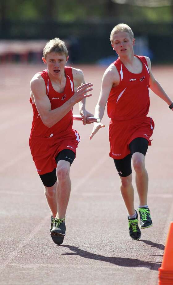 Mark Jaronbach takes the baton from teammate John Sulich for Greenwich High School in the boys 4x800 relay race in Greenwich, Conn. on Monday, April 22, 2013. Greenwich, which hosted the event, took second place in this race. Photo: J. Gregory Raymond / Stamford Advocate Freelance;  © J. Gregory Raymond