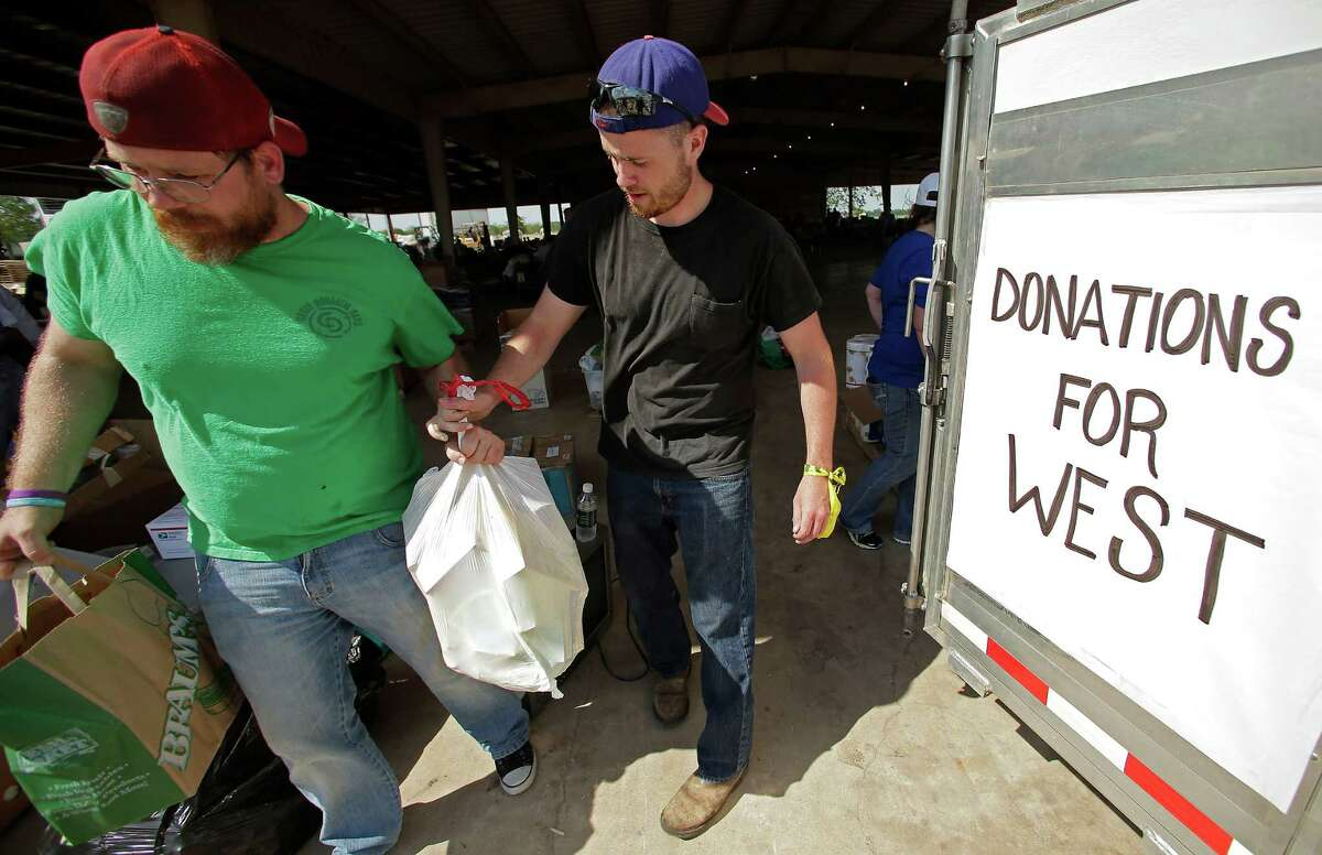 Volunteers unload goods donated for victims on Monday in West.