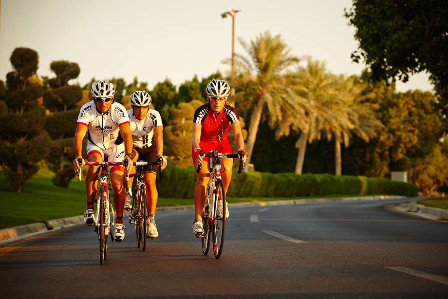 The benefits of an expatriate position extend to the entire family. Here, expats cycle in a Saudi Aramco community in Dhahran where Western-style conveniences, a fully accredited school system, medical care and recreational activities provide a small-town feel.