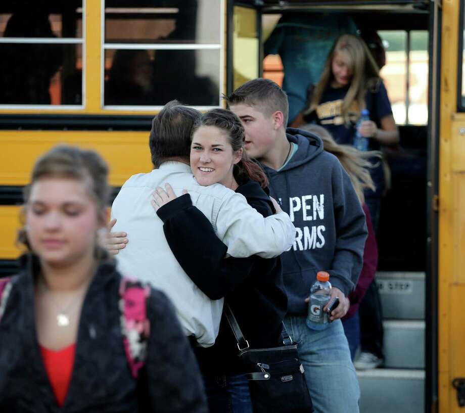 A high school student gets a hug from a teacher from West, Texas, as students arrive for classes at a temporary facility provided by the Connally Independent School District Monday, April 22, 2013, in Waco, Texas. West students returned back  to class today after a massive explosion at the West Fertilizer Co. five days ago damaged three of West's four schools, killed 14 people and injured more than 160 others. (AP Photo/Charlie Riedel) Photo: Charlie Riedel, Associated Press / AP