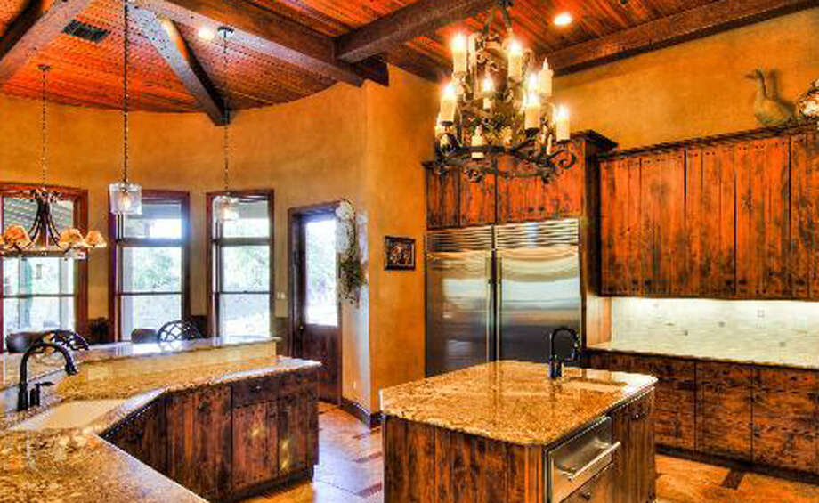 The kitchen features granite counter tops and chandelier lighting.