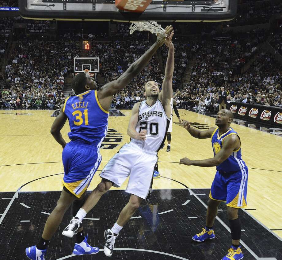 Manu Ginobili (20) of the Spurs shoots a layup as Festus Ezeli of Golden State attempts to block the shot during second-half NBA action at the AT&T Center on Wednesday, March 20, 2013. The Spurs won, 104-93. Photo: Billy Calzada, San Antonio Express-News