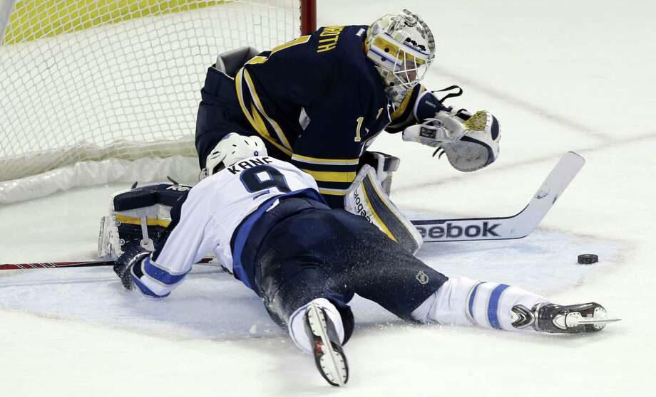 Buffalo Sabres goalie Jhonas Enroth of Sweden makes a save on a shot by Winnipeg Jets' Evander Kane (9) during the first period of an NHL hockey game in Buffalo, N.Y., Monday, April 22, 2013. Kane was tripped on the play and awarded a penalty shot. (AP Photo/David Duprey) Photo: David Duprey