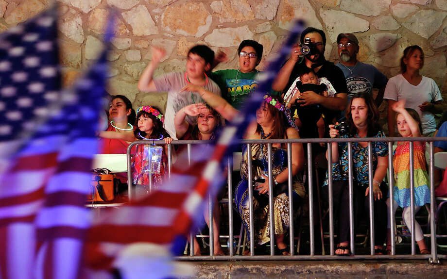 """Spectators watch the University of the Incarnate Word's """"Stars and Stripes"""" float pass during the Texas Cavaliers River Parade """"Stars on the River"""" held Monday April 22, 2013. Photo: Edward A. Ornelas, San Antonio Express-News / © 2012 San Antonio Express-News"""