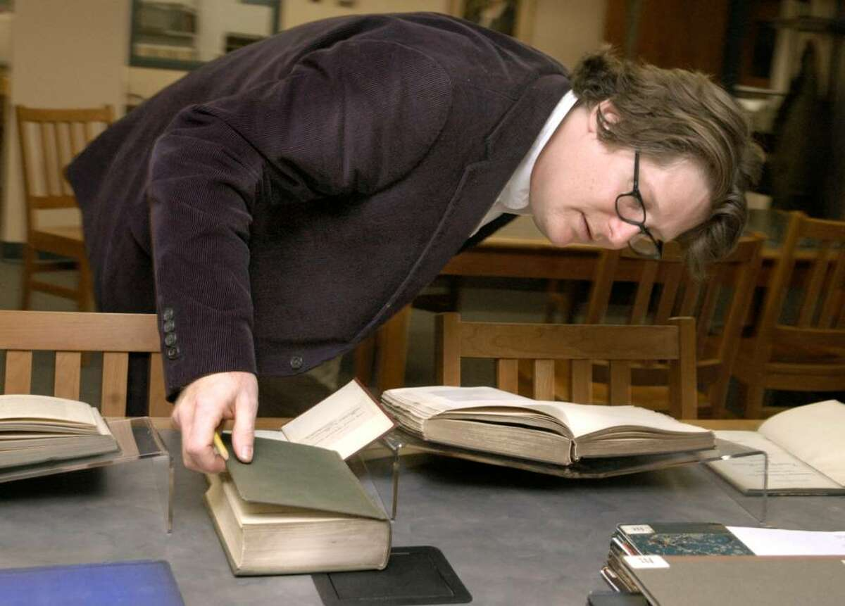 Brian Stevens, archivist for Western Connecticut State University, bends to examine the binder on one of the books in a collection about Connecticut History from the 1800's Thursday, January 7, 2010.