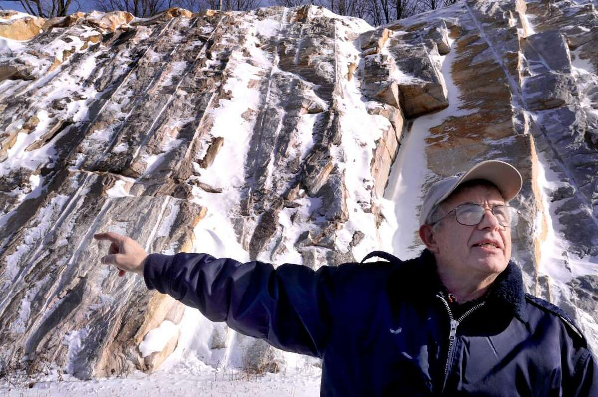 John Pawloski, 67, of the Danbury Mineralogists Club, points out the Stockbridge Marble, in rock formations along the new Rt. 7 bypass, in Brookfield, on Monday, Jan.4,2010.