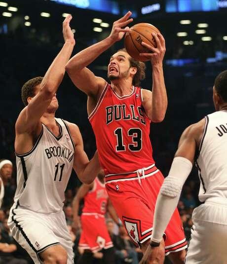 Chicago's Joakim Noah, who had 11 points, goes to the basket vs. Brooklyn's Brook Lopez (left). Photo: Nuccio DiNuzzo / Chicago Tribune