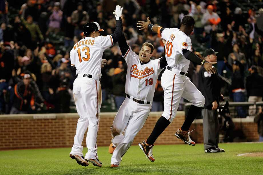 Chris Davis (19) celebrates with Manny Machado (13) and Adam Jones after scoring the O's winning run. Photo: Rob Carr, Staff / 2013 Getty Images