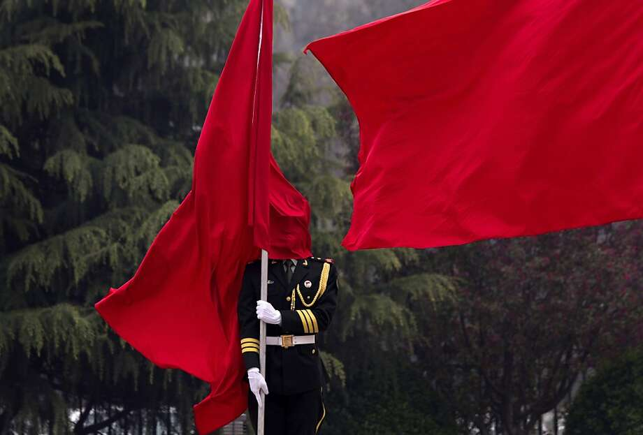 A honor guard is covered by a flag during a welcoming ceremony for U.S. Joint Chiefs Chairman Gen. Martin Dempsey at the Bayi Building in Beijing, China Monday, April 22, 2013. (AP Photo/Andy Wong, Pool) Photo: Andy Wong, Associated Press
