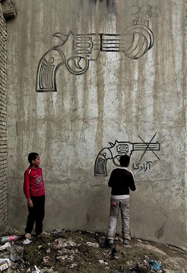 "Afghan boys look at graffiti on a wall on the outskirts of Kabul, Afghanistan, Monday, April 22, 2013. Persian, bottom right, reads, ""freedom."" (AP Photo/Rahmat Gul) Photo: Rahmat Gul, Associated Press"