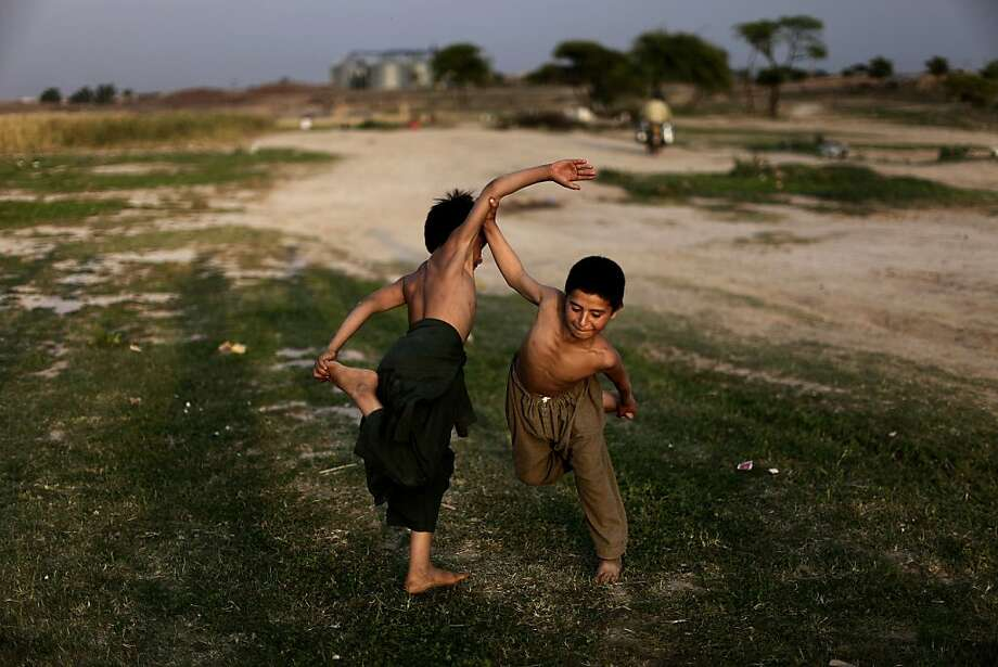 Afghan refugee boys, play a traditional fighting game, on the outskirts of Islamabad, Pakistan, Monday, April 22, 2013. Pakistan hosts over 1.6 million registered Afghans, the largest and most protracted refugee population in the world, according to the U.N. refugee agency. (AP Photo/Muhammed Muheisen) Photo: Muhammed Muheisen, Associated Press