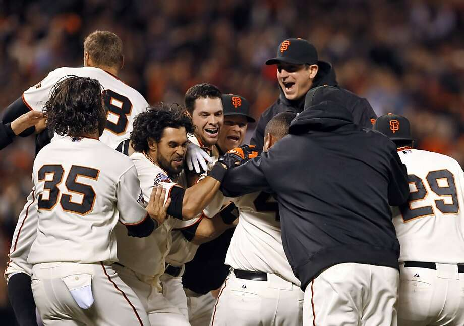 Brandon Belt (center) is mobbed by teammates after his single in the ninth inning scored Andres Torres with the winning run against the Diamondbacks. Photo: Carlos Avila Gonzalez, The Chronicle