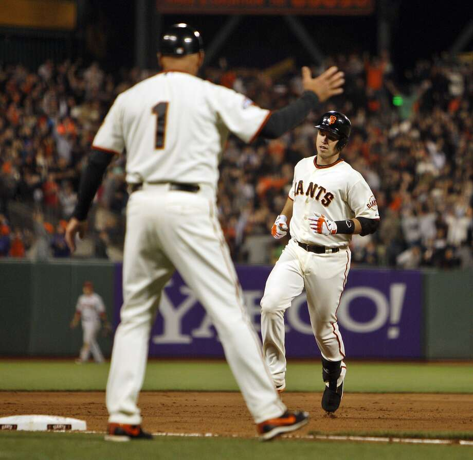 Besides giving signs, Tim Flannery gets to congratulate homer hitters like Buster Posey. Photo: Carlos Avila Gonzalez, The Chronicle
