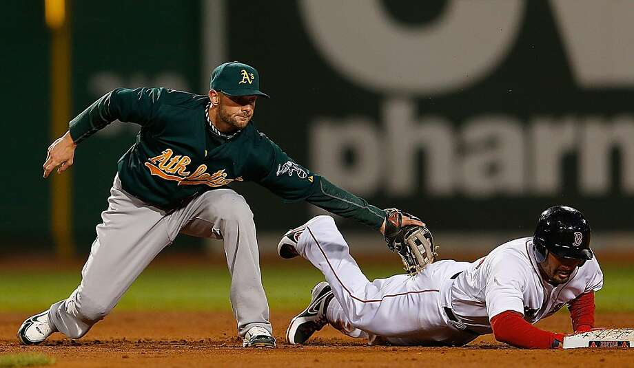 BOSTON, MA - APRIL 22:  Shane Victorino #18 of the Boston Red Sox leaps safely to the bag as Andy Parrino #12 of the Oakland Athletics slaps a late tag after dropping a ball thrown by the catcher in the 5th inning at Fenway Park on April 22, 2013 in Boston, Massachusetts.  (Photo by Jim Rogash/Getty Images) Photo: Jim Rogash, Getty Images