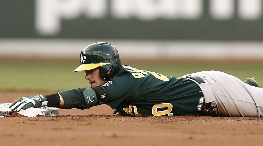 Oakland Athletics' Josh Donaldson hangs onto second base after a double during the second inning of a baseball game against the Boston Red Sox at Fenway Park in Boston on Monday, April 22, 2013. (AP Photo/Winslow Townson) Photo: Winslow Townson, Associated Press
