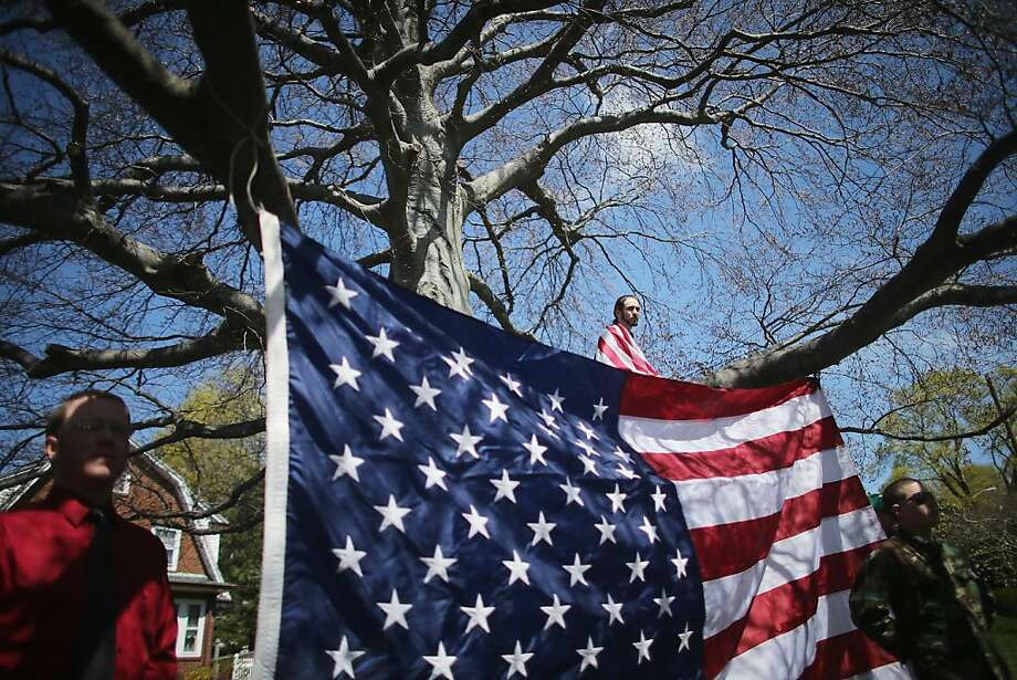 MEDFORD, MA - APRIL 22:  Devon Morancie (TOP) sits on a tree branch while wearing an American flag outside the funeral for 29-year-old Krystle Campbell, who was one of three people killed in the Boston Marathon bombings, on April 22, 2013 in Medford, Massachusetts. The 29-year-old restaurant manager was raised in Medford. Massachusetts Gov. Deval Patrick has asked residents to observe a moment of silence at the time of the first explosion at 2:50 p.m. this afternoon.  (Photo by Mario Tama/Getty Images) *** BESTPIX *** Photo: Mario Tama, Getty Images