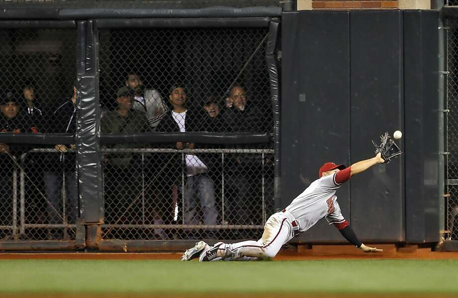 Cody Ross robs Buster Posey of a hit in the sixth inning. The San Francisco Giants played the Arizona Diamondbacks at AT&T Park in San Francisco, Calif., on Monday, April 22, 2013, winning 5-4 on a walk-off hit by Brandon Belt. Photo: Carlos Avila Gonzalez, The Chronicle