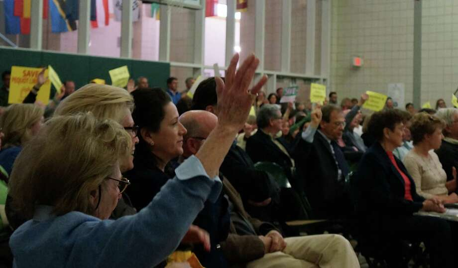 Waving signs and raising hands, a large crowd at Monday's Representative Town Meeting showed support for restoring $350,000 for the Pequot Library to the proposed 2013-14 town budget.   FAIRFIELD CITIZEN, CT 4/22/13 Photo: Genevieve Reilly / Fairfield Citizen