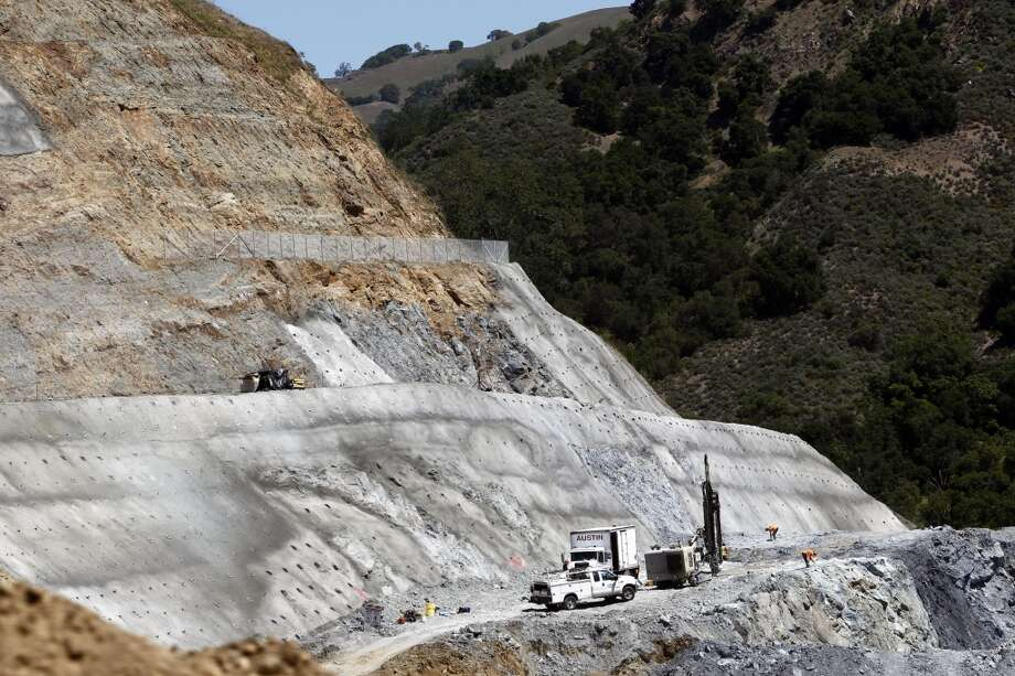 Workers (bottom right) place explosives deep into the ground to remove large areas of solid rock from the hillside to the West near where the left abutment of the dam will be at, as the Calaveras Dam Replacement Project continues to take shape on Thursday April 18, 2013, in Fremont, Ca. Construction on the project will be delayed two years and add $100 million to the cost due to the unstable ground beneath the dam. Calaveras Reservoir is San Francisco\'s largest storage site in the Hetch Hetchy water system.