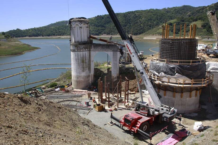 The old intake shaft tower, (left), on Thursday April 18, 2013, in Fremont, Ca. is being replaced with a new construction tower,  Construction on the Calaveras Dam Replacement Project  will be delayed two years and add $100 million to the cost due to the unstable ground beneath the dam. Calaveras Reservoir is San Francisco\'s largest storage site in the Hetch Hetchy water system.