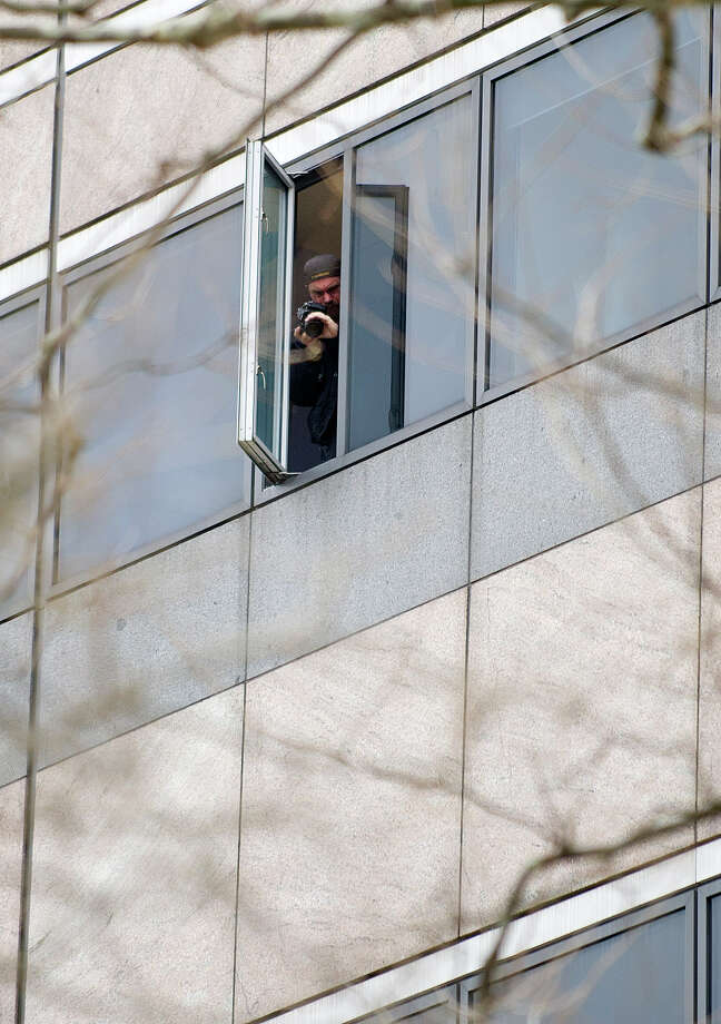 A police officer takes a photo from the window where a man committed suicide by jumping at Pitney Bowes in Stamford, Conn., on Tuesday, April 23, 2013. Photo: Lindsay Perry / Stamford Advocate