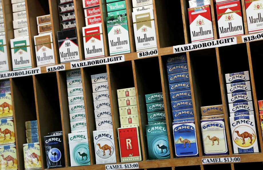 In this March 18, 2013 file photo cigarette packs are displayed for sale at a convenience store in New York. No one under 21 would be able to buy cigarettes in New York City under a proposal unveiled Monday, April 22, 2013 to make the city the most populous place in America to set the minimum age that high. (AP Photo/Mark Lennihan, file) Photo: Mark Lennihan